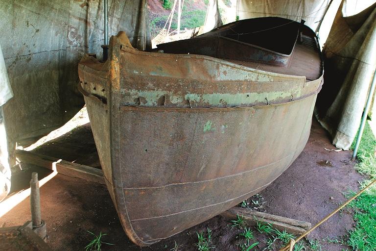 O histórico barco de ferro que foi tirado do fundo do rio agoniza em terra-firme
